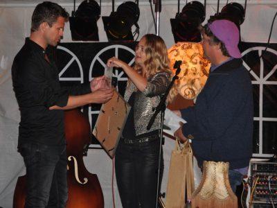 Wâldpykambadrice Tet Roozendaal overhandigt Wâldpyk certificaat aan Wâldpyk troubadour Marcel Smit; Rechts (met Brommelspet) Wâldpyk directeur Henk Pilat